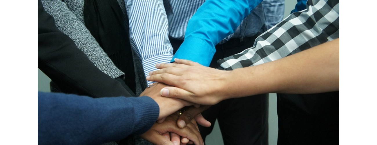 Group of people piling hands to evoke unity/teamwork.